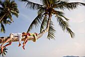Children lying on a palm tree, Rawa Island, Johor, Malaysia