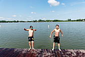 Two boys jumping baclwards into the lake, Inselsee, Guestrow, Mecklenburg-Western Pomerania, Germany