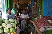 Laughing Sri Lankan vendors at a vegtable stall in Valaichchenai, next to Passekudah, Eastern Sri Lanka, South Asia