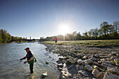 Angler and jogger at river Isar, Wittelsbach bridge in background, Munich, Bavaria, Germany