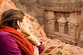 Woman lying on rock, Al Khazneh in background, Petra, Jordan, Middle East