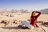 Woman resting on a rock, Wadi Rum, Jordan, Middle East