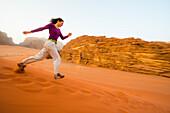 Woman running a sand dune down, Wadi Rum, Jordan, Middle East