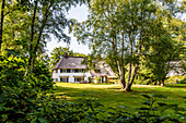 Thatched-roof house between deciduous trees, Hamburg, Germany