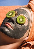Young woman with exfoliating face mask and slices of kiwi fruit on her eyes.