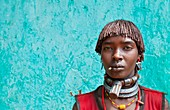 Dimeka Ethiopia Africa village Lower Omo Valley portrait of attractive Hamar woman with necklace showing First Wife against green wall 19