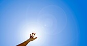 Arm and hand reaching out to sun