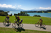 Family with bikes at Forggensee, Allgaeu Alps with Tegelberg, Saeuling and Tannheimer Berge in the background, Allgaeu, Bavaria, Germany