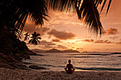 Yoga at sunset on Anse Severe beach, Palm trees, La Digue, Seychelles, Indian Ocean