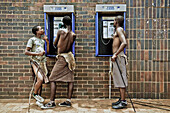 Three young men of the Swazi tribe at a telephone booth wearing traditional clothes, Swaziland, Africa