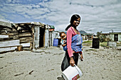 Young mother in front of shacks carrying her baby, Langa township, Cape Town, South Africa, Africa