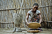Young mother from the Lozi tribe with baby sifting grain, Caprivi region, Namibia, Africa