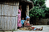 Two women and a child from the Lozi tribe in front of their hut, Caprivi region, Namibia, Africa