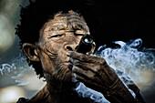Old woman from the San tribe smoking Dagga, Otjozondjupa region, Namibia, Africa