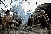 One Woman and four men from the San tribe sitting around a campfire, Otjozondjupa region, Namibia, Africa