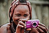 Woman of the Himba tribe holding a modern camera, Kaokoland, Namibia, Africa