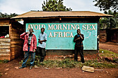 Three men smoking pipes in front of a hut with Anti-Aids campaign, Buwenda, Uganda, Africa