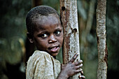 Young girl leaning against a tree, Uganda, Africa