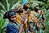 Women in a Pygmy village singing and clapping, Lake Bunyonyi, Uganda, Africa