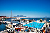 View over swimming pool and harbour towards Vesuvius, Naples, Bay of Naples, Campania, Italy