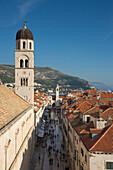 Blick von der Stadtmauer auf Fußgänger in der Stradun Hauptgasse der Altstadt mit Kirchturm von Franziskanerkloster, Dubrovnik, Dalmatien, Kroatien, Europa