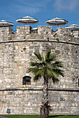 Palm tree and parasols of a cafe on the roof of the old fortress tower, Durres, Albania