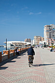 Man riding his bicycle along the Durres seafront promenade, Durres, Albania