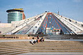 People sitting on the steps of the graffiti-covered The Pyramid International Center of Culture with glass high-rise building of Austrian Raiffeisen Bank behind, Tirana, Albania