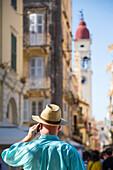 Mann mit Sonnenhut und Mobiltelefon vor Kirchturm der Kirche Sankt Spyridon in Altstadt, Kerkyra, Stadt Korfu, Korfu, Ionische Inseln, Griechenland, Europa