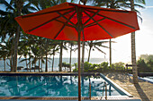 Parasol and pool under palm trees with sea view, Turtle Bay Hotel, Tangalle, South Sri Lanka