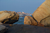 View to temples on a rocky hill on the coast, rocks on the beach at Kirinda near Gala National park, South Sri Lanka