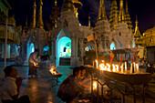Burmese people lighting candles at the Shwedagon Paya, Yangon, Rangoon, Myanmar, Burma