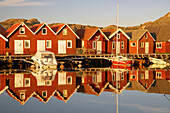 Boats and boot houses in Bleket port reflecting in the water, Tjoern Island, Province of Bohuslaen, West coast, Sweden, Europe