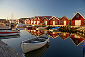 Boats and boot houses in Bleket port, with reflection in the water, Tjoern Island, Province of Bohuslaen, West coast, Sweden, Europe