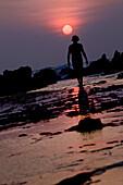 Man walking along beach in sunset, Jakarta, Java, Indonesia