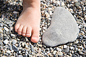 Foot of child next to a pebble at shingle beach, Andalusia, Spain