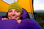 A young woman smiles in her sleeping bag and tent while camping in Grand Teton National Park, Wyoming Jackson, Wyoming, USA