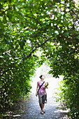 A young woman stands in an arch of greenery while holding her yoga mat Seattle, Washington, USA