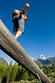 A young man hiker balances on an old log in the Grand Teton National Park, Wyoming Wyoming, USA
