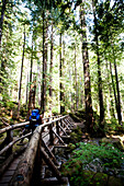 A young girl crosses a wooden bridge while carrying a large backpack, Washington, USA