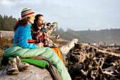 Two beautiful women and drink a beer while enjoying the sunset at La Push Beach, from a drift log La Push, Washington, USA