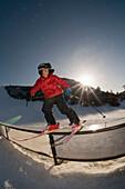 A young boy riding the rails with his skis in Durango, Colorado Durango, Colorado, USA