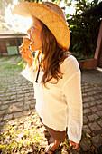 A woman in a cowboy hat eats ice cream in the sun in Brazil Brazil