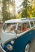 A young man and woman pose for a picture from inside their vintage van Sandpoint, Idaho, USA