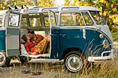 A young couple kiss inside of their classic van Sandpoint, Idaho, USA