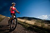 A female mountain biker stops to enjoy the view while riding the trails of Mt. Sentinel, Missoula, Montana Missoula, Montana, USA