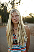 A pre-teen girl with long blond hair poses for the camera in Maui, Hawaii on an early morning at Paia Beach Maui, Hawaii, USA