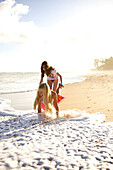 Two pre-teen girls play at Paia Beach, Maui, Hawaii and laugh as the wave gets them wet Maui, Hawaii, USA