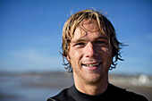Young male surfer at Pacific Beach in San Diego, California on a sunny day smiles and look straight at the camera San Diego, California, USA
