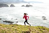 Woman trail running along the Oregon coast Cannon Beach, Oregon, USA